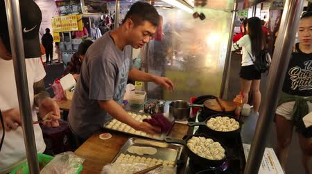 songshan : TAIPEI, TAIWAN - DECEMBER 4, 2018: Vendors prepare Chinese food xiao long bao dumplings at Raohe Night Market in Taipei. Night food markets are a big part of Taiwanese culture.