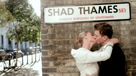 csókolózás : Just married couple kissing against a wall under a London city sign