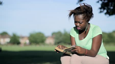 záložka : African woman sits on a log reading a book closer frame