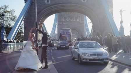 double happiness : Just married couple dancing on London Bridge among passersby