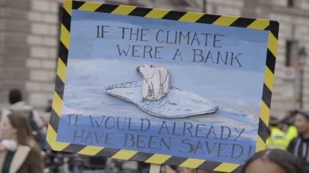 London, UK - October 12th, 2019 : Climate Change Protest Sign, Woman carrying a sign reading If the climate were a bank, it would have been saved already at a climate change protest in London, UK.