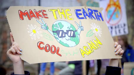 London, UK - October 12th, 2019 : Make the Earth Cool Again Protest Sign, Hands holding up a sign reading Make the Planet Cool Again at a climate change protest in London, UK.