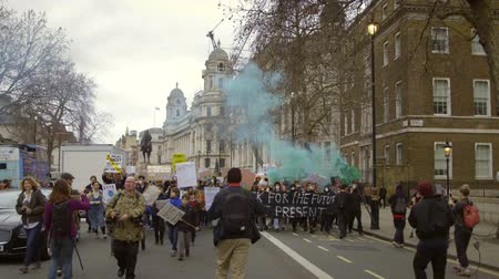 London, UK - October 12th, 2019 : Youth Strike Climate Change March, Activists marching with coloured powder paint to protest climate change inaction in London, UK.