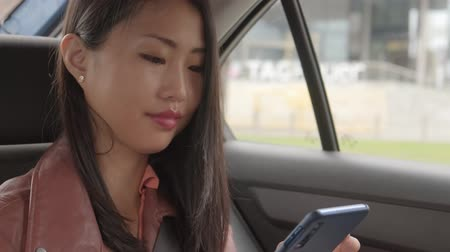 Woman at the Backseat of a Car and Texting
