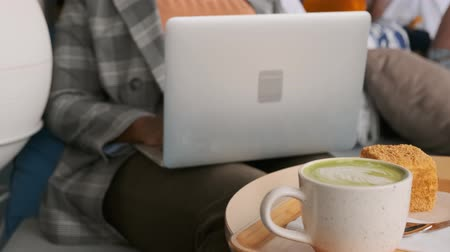 A Woman Working On Her Laptop Inside A Cafe Orders Coffee And Pastry