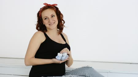 booties : Red-haired young woman with a red bandana on her head holding booties. Smiles.