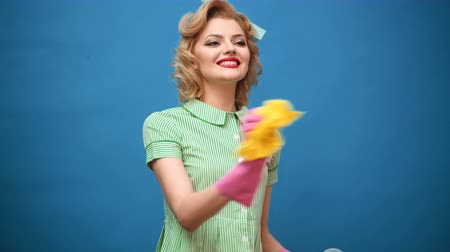 pinup : Pin up woman in gloves smiling and wiping dust using a spray and a duster. Cleaning concept with supplies. Beautiful young woman makes cleaning. Pin up cleaning. Beautiful woman in gloves cleaning.