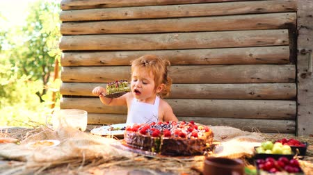torty : Cute little boy in white pinafore eats fruit cake and cup of milk at table outdoors on wooden.