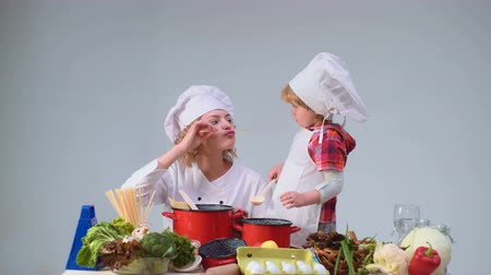 filha : Cute little boy and his beautiful mother smiling while cooking in kitchen. Young family cooking food in kitchen. Young mother and son cooking meal together.