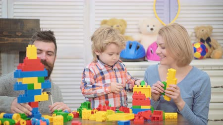 три человека : Young family in playroom. Love family concept. Mom, dad and boy with toys build out of plastic blocks. Parents and son smiling, make brick constructions.
