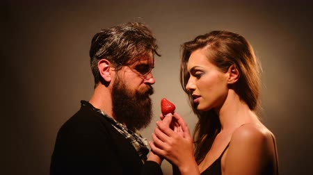 desire : young sexy couple of woman with pretty face and brunette hair with bare shoulders and handsome bearded man with long beard eating red strawberry berry fruit Stock Footage