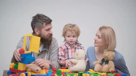 три человека : Young family play game with construction plastic blocks. Family games concept. Parents and kid with happy faces hold red bricks. Father, mother and son in playroom on light wooden background