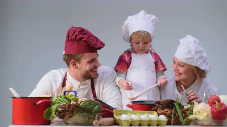filha : Cute little boy and his beautiful parents are smiling while cooking in kitchen. Young family cooking food in kitchen. Happy family cooking together. Happy young family with Mum, Dad child cooking.