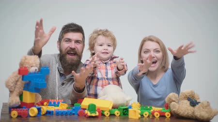 три человека : Young family play game with construction plastic blocks. Family games concept. Parents and kid with happy faces hold red bricks. Father, mother and son in playroom on light wooden background.