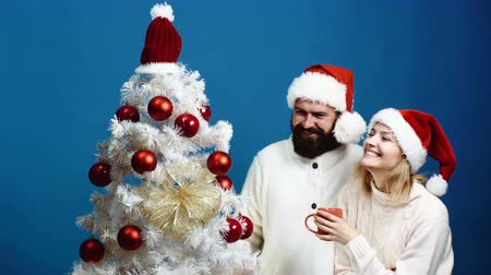 new clothes : Loving couple with happy faces meet New Year near Christmas tree. Young couple in New Years hats decorate a Christmas tree on a blue background. New Years Concept.