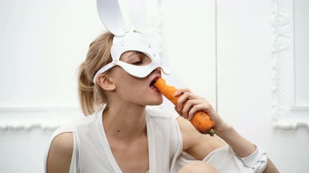 útil : Close up of a girl dressed in a mask of a hare that eats carrots on a white background. Concept of healthy food.