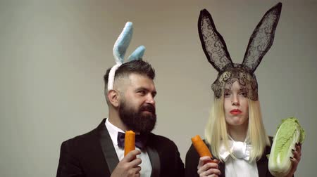 koszyk wielkanocny : Rabbit couple eat carrot. Bunny ears concept with bunny couple. Heppy easter couple. Rabbit man and woman surprise emotions. Wideo
