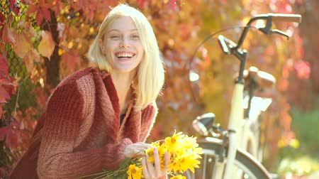 leafs : Woman with yellow flovers. Autumn happy girl and joy. Dreamy girl with long hair in knit sweater. Autumn woman with retro bike with flowers in basket in autumnal park. Clouse up portrait of girl.