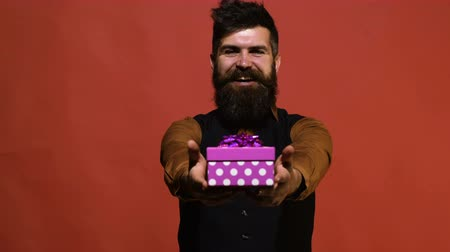 presentes : Bbearded man holds a New Years gift in his hand n red background. Concept of celebration new year. Man presents a gift in a box on a red background. Concept of valentines day.
