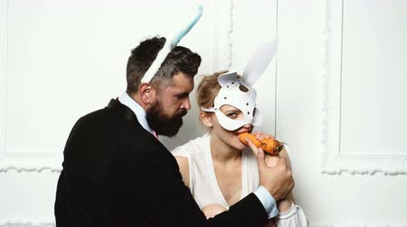 tükenme : Bearded man in a suit feed woman by carrot who is dressed in a leather mask on white background. Fashion concept. Stok Video