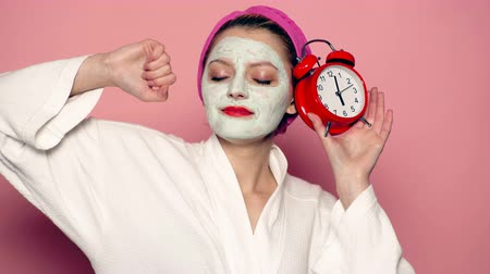 質地 : Girl with a mask on his face holds a clock in his hand on a pink background. Concept of skin care.