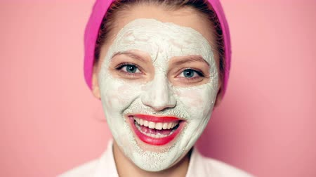 az emberi bőr : Girl in a cosmetic mask with a towel on her head smiles at the pink background. Beautiful girl with cosmetic mask on her face. Face care concept.
