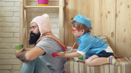 pediatria : Happy healthy child is played by a doctor. Doctor and his patient. Boy dressed in a doctor listens to a patient with a stethoscope.