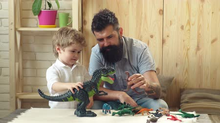 образовательный : Man and boy play together on wooden wall background. Family and childhood concept. Father and son play with toys dinosaurs.