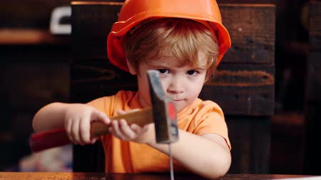 trabalhador manual : Childrens creativity engineering education - boy in workshop. Little boy in helmet clogs the nail. Little builder concept. Vídeos
