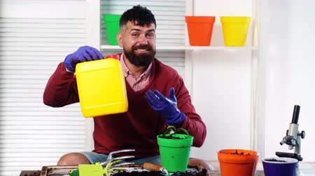 blízkost : Smiling bearded man holds a plastic canister in his hands, and in another hand holds a pot with a plant. Gardening concept.
