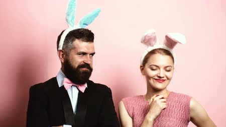 соблазнять : Bearded man with ears hare and blond woman with ears hare eating an apple on a pink background. A woman with rabbit ears offers an apple to her husband with rabbit ears.