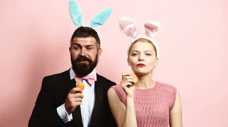 kostüm : Bearded man and girl with rabbit ears eat carrots and an apple on pink background. Hares eat fruits. Concept of healthy eating.