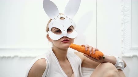 provokativní : Girl in a leather mask eating carrots on a white background. Passionate woman in a leather mask. Hot girl with thick carrots in her hand.