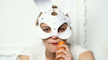 интимный : Close up of a girl in a leather mask who eats a carrot. Girl temptingly eats carrots. Close up of a girl in a leather mask who takes a thick carrot in her mouth.