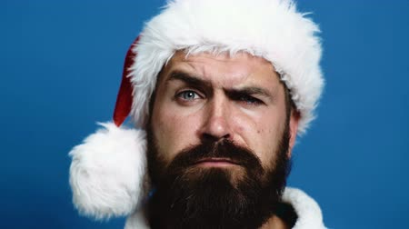 борода : Close-up of a bearded man in a New Years hat which moves his eyebrows. Bearded man moves his eyebrows on a blue background. Holidays celebration concept.