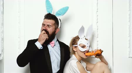 easter : Bearded man wearing in a suit and rabbit ears eats an apple with a woman dressed in a leather mask who eats a carrot. Fashionable couple eats fruit on white background.