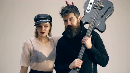 biustonosz : Bearded man with a guitar and a woman in a leather hat are looking at each other. Hard rock couple with guitar. Woman wearing a leather hat makes horns by bearded man with a guitar. Wideo