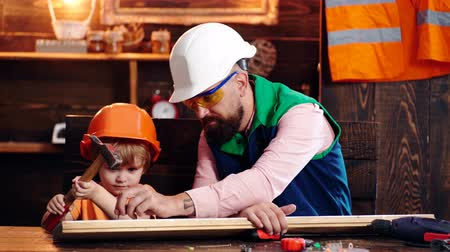 repairer : Father with beard teaching little son to use tools. Boy, child in protective helmet learning to use hammer with dad. Little assistant concept.