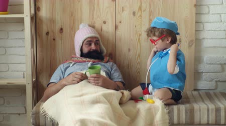 ilk yardım : Father and son playing clinic at home. Medical education concept. Doctor with stethoscope examining bearded man. Kid and father playing hospital. Patient with flu lying in bed under woolen blanket. Stok Video