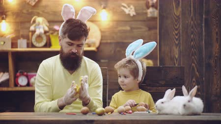 yay : Bearded man and his son dressed in rabbit ears adorn Easter eggs. Father and son are painting eggs. Happy family are preparing for Easter. Cute little child boy wearing bunny ears. Happy easter.