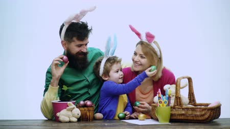koszyk wielkanocny : Mother, father and son are painting eggs. Happy family are preparing for Easter. Cute little child boy wearing bunny ears.