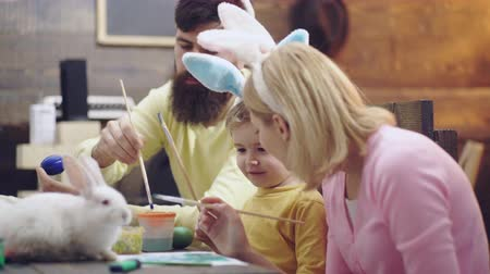 koszyk wielkanocny : Mother, father and son are painting eggs. Happy family are preparing for Easter. Cute little child boy wearing bunny ears. Happy easter. Easter bunny. Easter eggs on wooden background.