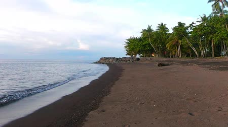 The beach of black sand and sunset. Camiguin Island. Philippines.