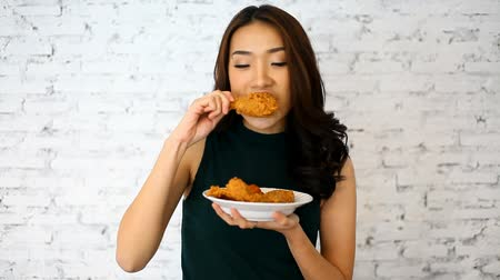dobverő : Attractive Asian woman eating fried chicken drumstick over white brick background