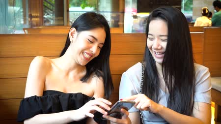 telefonda : Two Asian female friends using mobile phone and laughing together. Women enjoying good time at Japanese restaurant