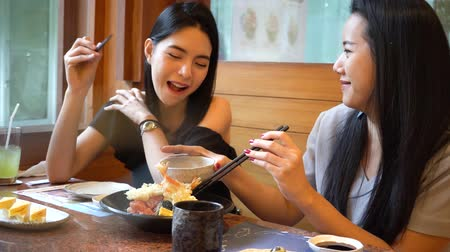 kínai evőpálcikák : Two Asian female friends eating and having a meal together. Women enjoying good time at Japanese restaurant