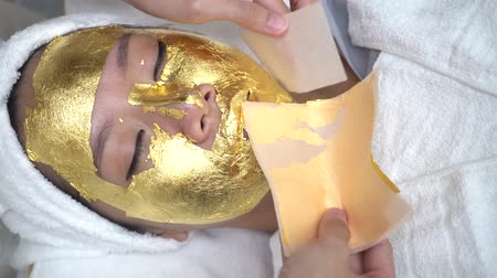 fiatalos : Young woman getting 24 karat gold facial treatment at the beaty clinic. The treatment of using real gold for youthful skin Stock mozgókép