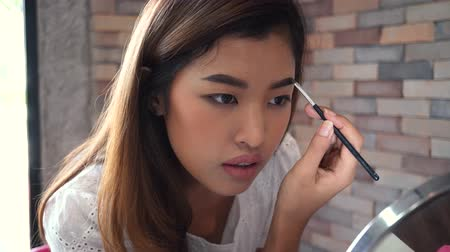 eyebrow correction : Closeup young Asian model painting eyebrow by brush on blurred background Stock Footage