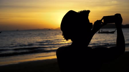 фотографий : Silhouette back of young male travel backpacker with hat taking photos of summer beach scenery against sunset - travel picture moment captured concept.