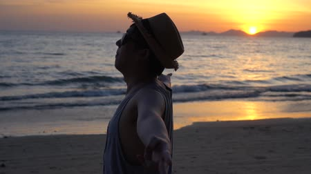 bajnok : Silhouette back of young male travel backpacker doing peace v sign finger and turning around against sunset and tropical summer ocean beach background. Stock mozgókép